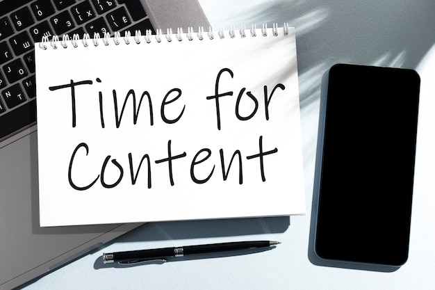 ノートブック、ラップトップ、ペン、携帯電話のコンテンツのテキスト時間。ビジネスコンセプト。フラットレイ。