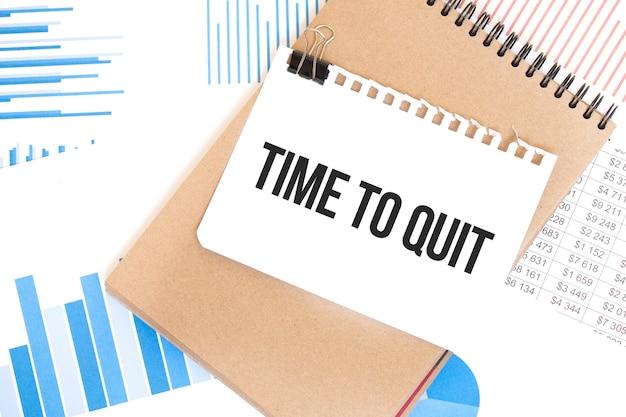 Text time to quit on white paper sheet and brown paper notepad on the table with diagram