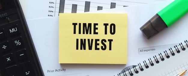 Текст «время инвестировать» на странице блокнота, лежащего на финансовых диаграммах на офисном столе. рядом с калькулятором.