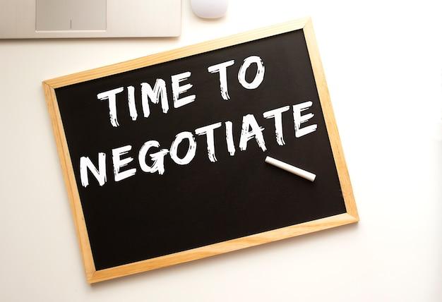 슬레이트 보드 사무실 책상에 분필로 쓰여진 협상 시간 텍스트