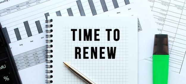 사무실 책상의 재무 차트에있는 메모장 페이지에 time to renew라고 문자를 보냅니다. 계산기 근처.