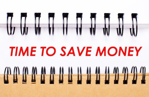 Текст «время экономить деньги» на белой бумаге между белыми и коричневыми спиральными блокнотами.