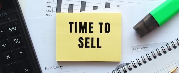 オフィスの机の財務チャートにあるメモ帳のページに「販売時間」とテキストを入力します。電卓の近く。ビジネスコンセプト。