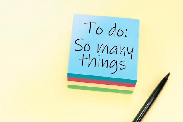 Текст «делать так много вещей», написанный от руки черной ручкой на синем стикере.