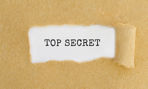 Text top secret appearing behind ripped brown paper.