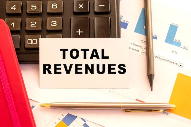 金属製のペン、電卓、財務チャートを使用して、白いカードに総収益をテキストで送信します