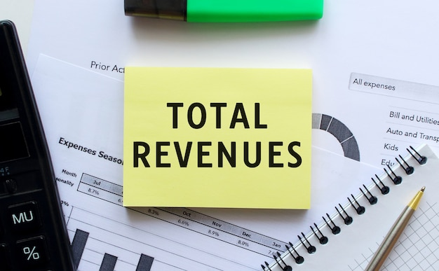 Text total revenues on the page of a notepad lying on financial charts on the office desk.