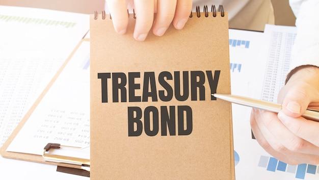 図とテーブルの上のビジネスマンの手で茶色の紙のメモ帳に財務省債をテキストで送信します。