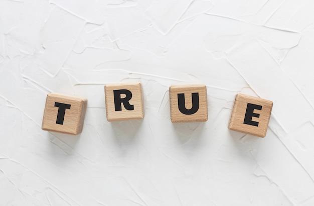 Текст истина из деревянных кубиков на белом фоне замазки. квадратные деревянные блоки. вид сверху, плоская планировка.