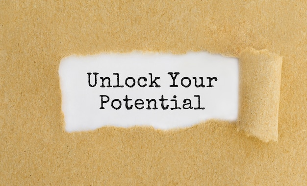 Text unlock your potential appearing behind ripped brown paper.