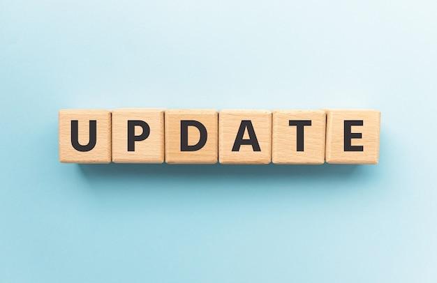 青い背景の上の木製の立方体のテキストの更新。正方形のウッドブロック。上面図、フラットレイ。