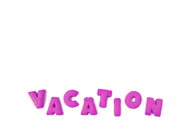 Text of vacation spelled with purple alphabet shaped biscuits on a white background