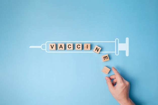 Текст «вакцина» на деревянном блоке с изолированным значком шприца