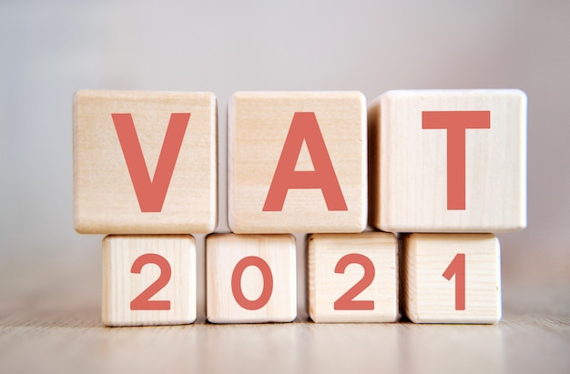 Text  vat 2021 on wooden cubes, on wooden background.