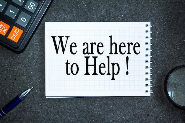 Текст мы здесь, чтобы помочь. офисный стол, калькулятор, блокнот с документами. бизнес-концепция
