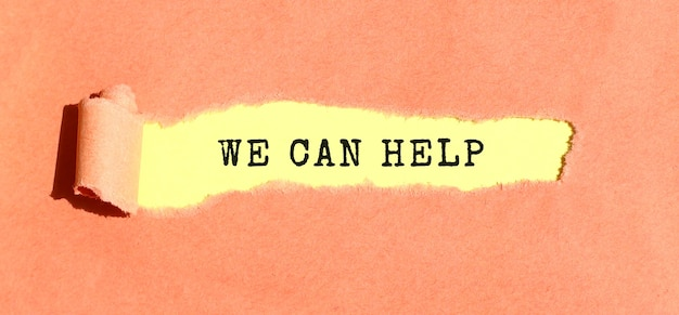 The text we can help appearing on yellow paper behind torn color paper. top view.