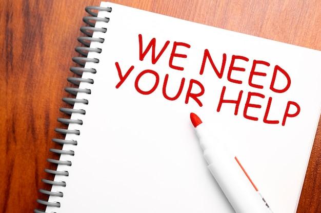 Текст, который нам нужна ваша помощь, написанный в блокноте, офисном деревянном столе и красным маркером сверху, концептуальное изображение для заголовка блога или изображение заголовка. выдержанный винтажный цвет.