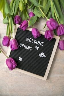 レターボードと紫色のチューリップの花の花束に春を歓迎するテキスト Premium写真