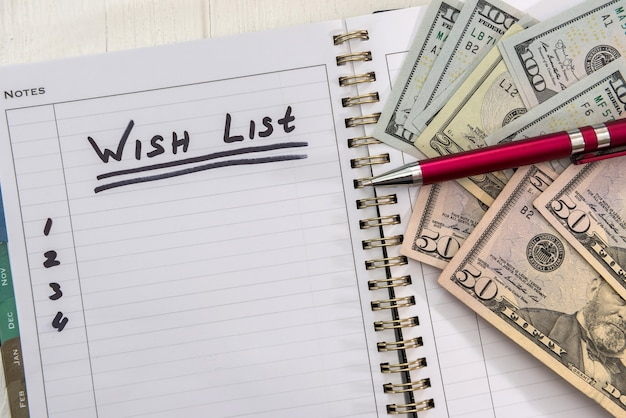 Text wish list  on notepad with dollar bills. plan for future