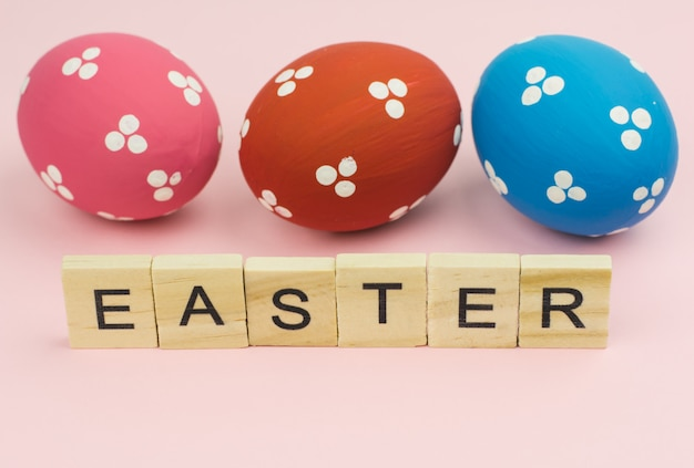 Text wooden blocks spelling the word easter on pink background