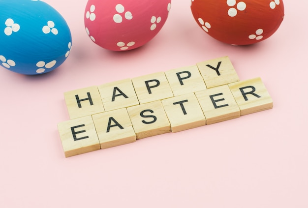 Text wooden blocks spelling the word happy easter on pink background