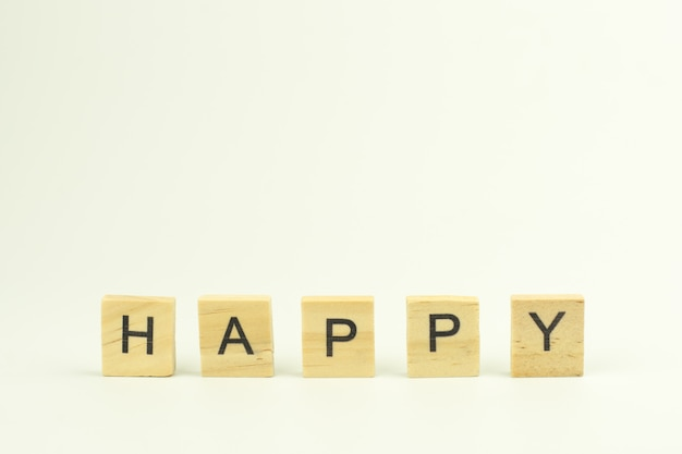 Text wooden blocks spelling the word happy on white background