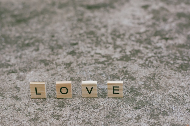 Text wooden blocks spelling the word love on textured concrete background