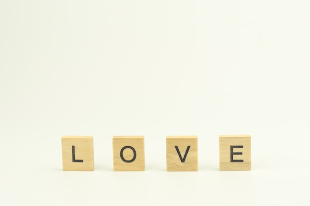 Text wooden blocks spelling the word love on white background