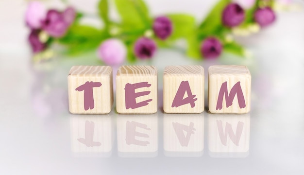 Text of the word team on wooden cubes by light wooden table. flowers in the background