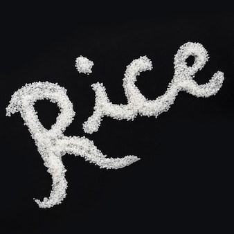 Text written with uncooked rice on black background