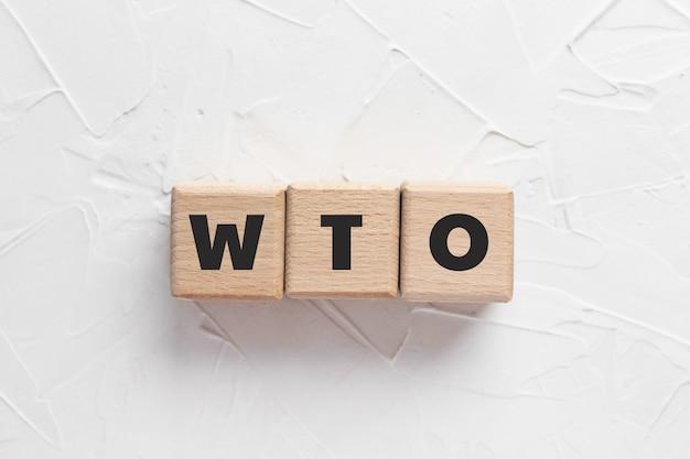 Текст вто на деревянных кубиках на белом текстурированном фоне замазки. аббревиатура «всемирная торговая организация». квадратные деревянные блоки. вид сверху, плоская планировка.