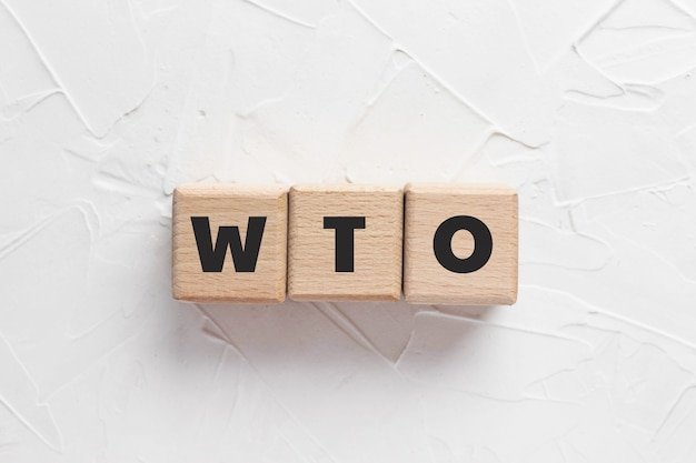 Text wto on wooden cubes on white textured putty background. abbreviation of 'world trade organization'. square wood blocks. top view, flat lay.