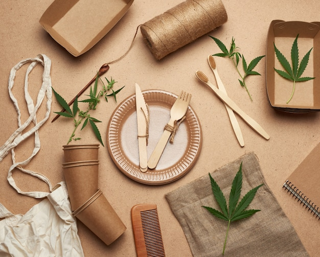 Textile bag and disposable tableware from brown craft paper, green hemp leaves on a wooden background