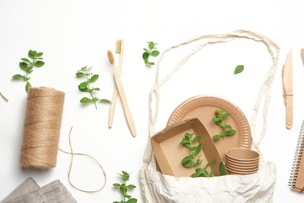 Textile bag and disposable tableware from brown craft paper, green mint leaves on a whitebackground. view from above