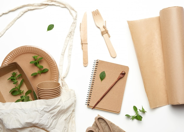 Textile bag and disposable tableware from brown craft paper, green mint leaves on a whitebackground