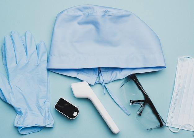 Текстильная синяя кепка, одноразовая медицинская маска, пара перчаток и пластиковые очки на синем, вид сверху. защитная одежда медика