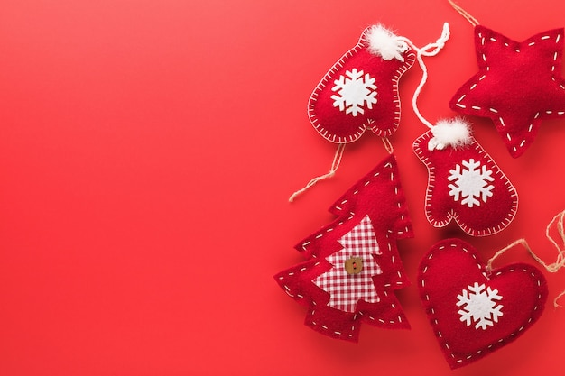 복사 공간이 있는 빨간색 배경의 오른쪽에 있는 섬유 크리스마스 장난감