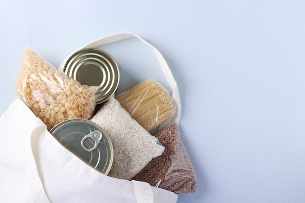 水色の背景に食料品が入ったテキスタイル食料品バッグ。米、そば、パスタ、缶詰。フードデリバリー、寄付、コピースペース