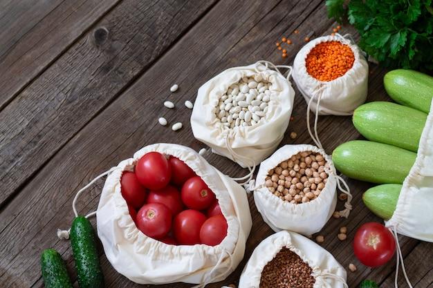 Текстильные продуктовые сумки с крупами и свежими овощами на деревянном столе наверху. концепция пожертвований еды или еды