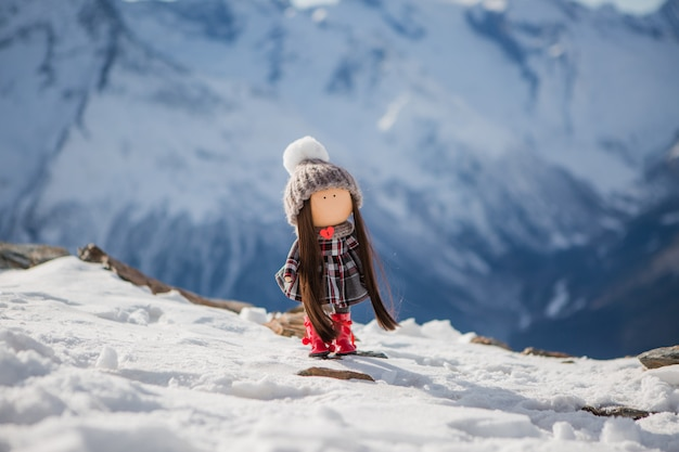 Textile handmade doll in winter clothes