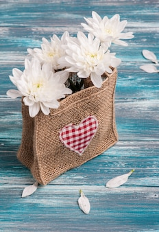 Textile heart and bouquet of flowers in rough burlap bag