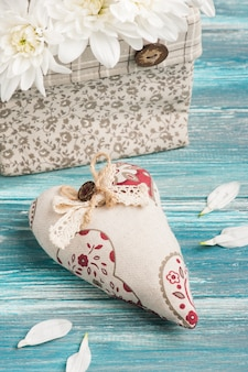 Textile heart and bouquet of flowers in rough linen bag