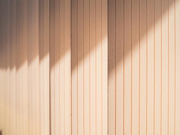 日光の光線で窓を覆う垂直ブラインドのテキスタイルラメラ