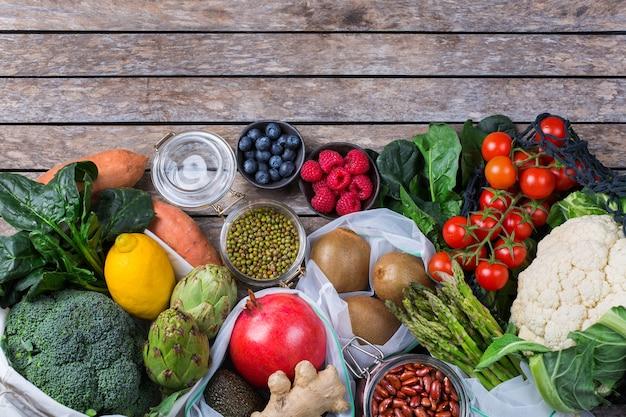農産物、果物、野菜が入ったテキスタイルメッシュバッグ。ゼロウェイスト、環境にやさしい、プラスチックフリーのリサイクル、再利用可能、持続可能な食料品の買い物のコンセプト。コピースペース、フラットレイの背景