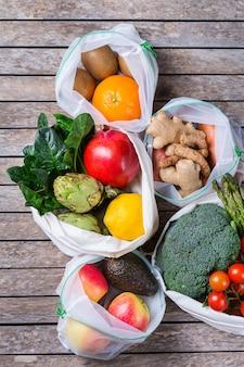 農産物、果物、野菜が入ったテキスタイルメッシュバッグ。ゼロウェイスト、環境にやさしい、プラスチックフリーのリサイクル、再利用可能、持続可能な食料品の買い物のコンセプト。フラットレイの背景