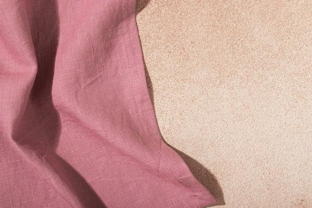 베이지색 회반죽 배경에 분홍색 직물 서빙 냅킨