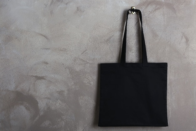 Textile shopping bag hanging on color wall
