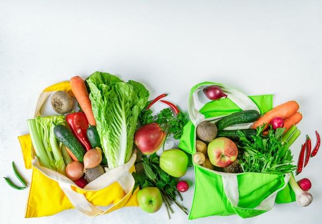 カラフルな野菜や果物がいっぱいのテキスタイルショッピングバッグ。健康的な食事や春のデトックスコンセプト