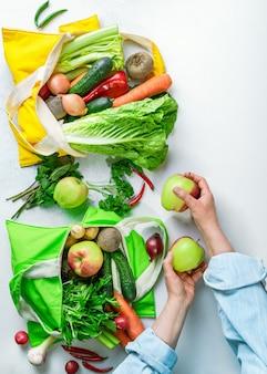 カラフルな野菜や果物がいっぱい入ったテキスタイルのショッピングバッグ、女性の手がバッグを開梱する