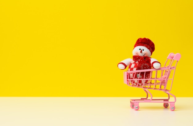 Textile snowman in a metal miniature shopping cart on a white table, yellow background. festive background for christmas and new year, copy space